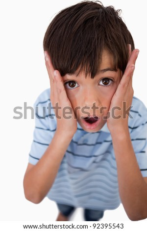 Portrait of a shocked  boy looking at the camera against a white background