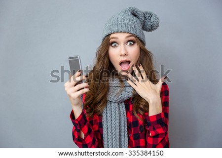 Portrait of a shocked woman holding smartphone over gray background - stock photo