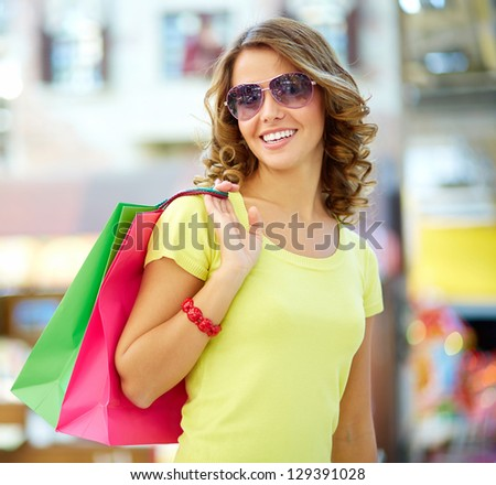 Portrait of a shopping young woman wearing cool sunglasses - stock photo