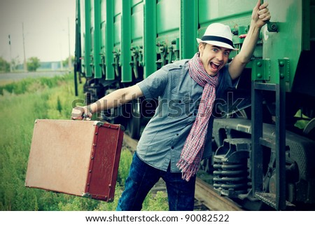 Portrait of a shouting young man holding a train.