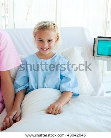 Portrait of a sick little girl on a hospital bed - stock photo