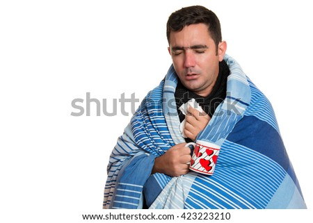 Portrait of a sick man with a fever wrapped in a blanket and holding a warm tea cup - stock photo