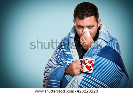 Portrait of a sick man with the flu, allergy, germs,cold, blowing his nose with tissue and holding a warm tea cup - stock photo