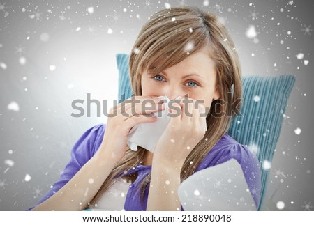 Portrait of a sick pretty woman blowing lying on a sofa against snow falling - stock photo