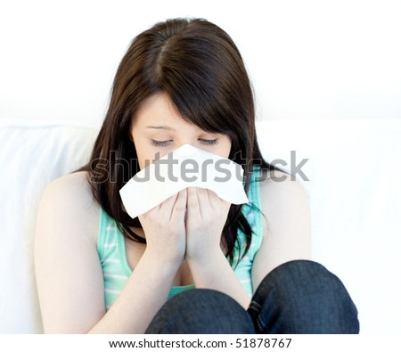 Portrait of a sick teen girl blowing sitting on a sofa
