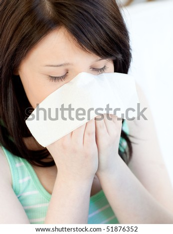 Portrait of a sick tired teen girl blowing sitting on a sofa - stock photo