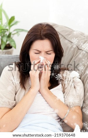 Portrait of a sick woman blowing her nose while sitting on the sofa with snow falling