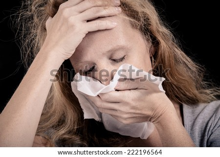 Portrait of a sick woman covering the face with a napkin