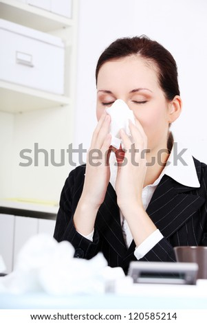 Portrait of a sick young business woman blowing her nose.