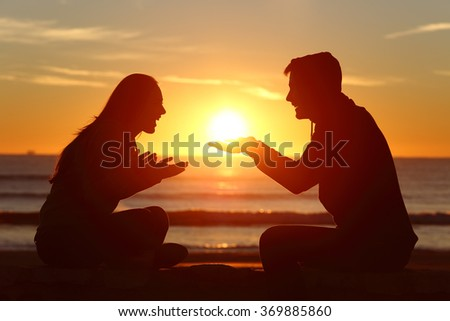 Portrait of a side view of couple or friends silhouette dating and falling in love with a boyfriend giving the sun to his girlfriend outdoors at sunset - stock photo