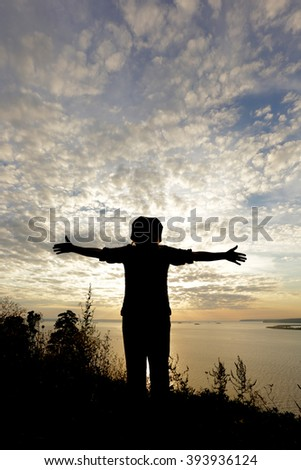 Portrait of a silhouette of a man on the river bank at sunset background - stock photo