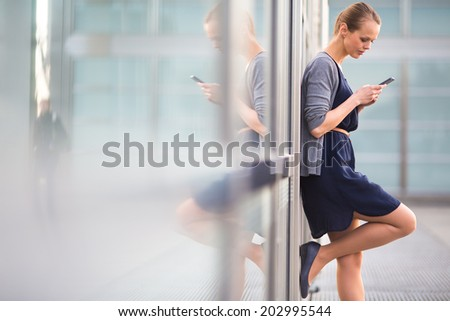 Portrait of a sleek young woman calling on a smartphone and using her laptop in a an urban/city context (shallow DOF; color toned image) - stock photo