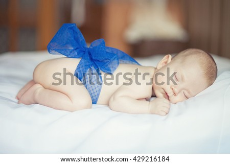 portrait of a sleeping child with a small blue bow