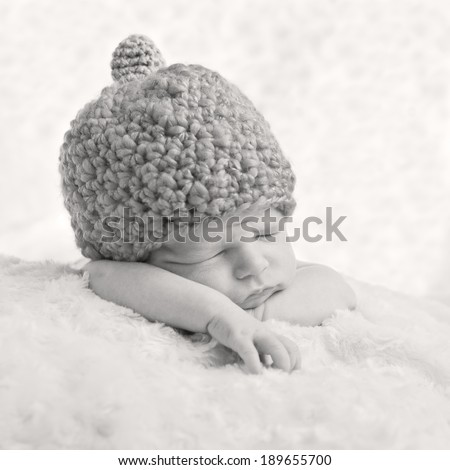 Portrait of a sleeping newborn baby in a knitted hat ( black and white ) - stock photo