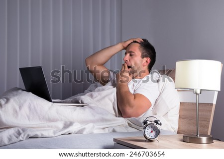 Portrait Of A Sleepy Man Yawning On Bed Looking At Laptop - stock photo