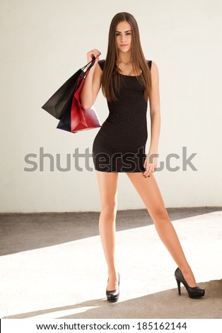 Portrait of a slender young brunette beauty holding shopping bags.
