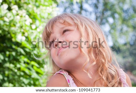 Portrait of a slightly smiling little blond beautiful Russian girl above nature outdoor background