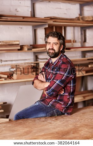 Portrait of a small business owner sitting on the edge of his workbench, looking at the camera with his arms crossed confidently, with workshop shelves in the background with planks of wood - stock photo