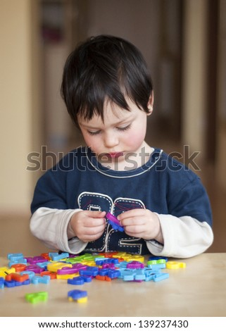 Portrait of a small child, boy or girl, playing with colorful plastic letters. - stock photo