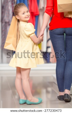 Portrait of a small girl standing in a fashion store holding the hand of her mother and packages