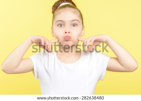 Portrait of a small pretty girl standing and blowing her cheeks and holding her forefingers close to them wearing a white t-shirt with big bun hairstyle, isolated on a yellow background - stock photo