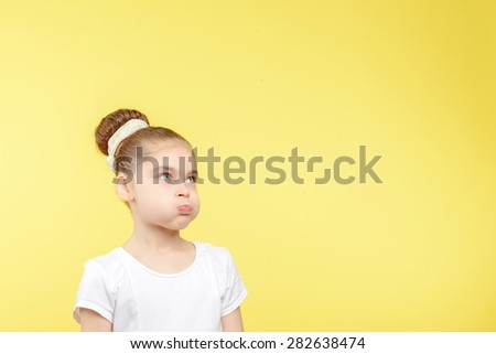 Portrait of a small pretty girl standing and blowing her cheeks looking sad or exhausted wearing a white t-shirt with big bun hairstyle, isolated on a yellow background - stock photo