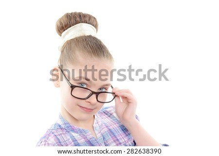 Portrait of a small pretty girl wearing reading glasses looking from under black spectacle frame smiling wearing colorful checkered shirt with big bun hairstyle ,isolated on a white background - stock photo