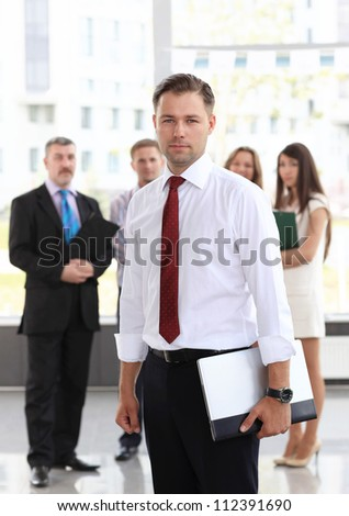 Portrait of a smart business man using laptop with colleagues in the background