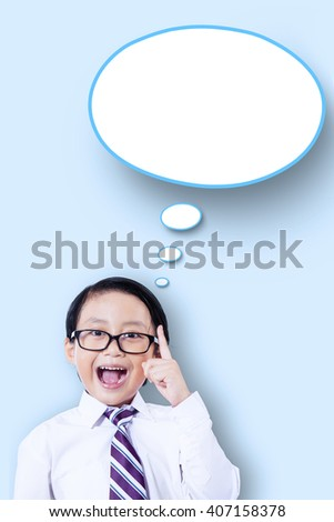 Portrait of a smart little boy having idea and pointing at empty speech bubble - stock photo