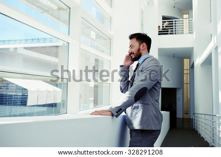 Portrait of a smart man managing director dressed in corporate clothing talk on mobile phone while rest after briefing, handsome intelligent male economist calling on cell telephone during work break   - stock photo