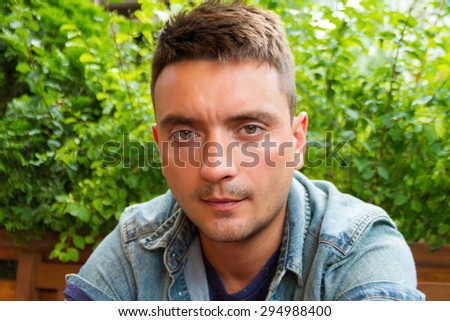Portrait of a smart serious young man with stylish haircut seating against nature green leaves background. Handsome brunette student man outdoors portrait. Portrait of trendy guy in jeans shirt.  - stock photo