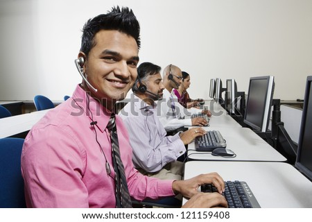 Portrait of a smart young customer service operator with colleagues in the office - stock photo