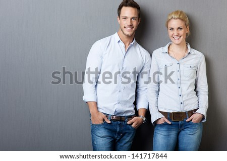 Portrait of a smart young man and woman standing against gray background - stock photo