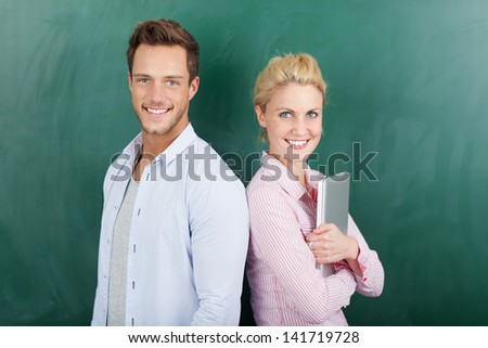 Portrait of a smart young man and woman with laptop standing against green background - stock photo