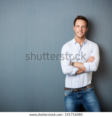 Portrait of a smart young man standing with arms crossed against gray background - stock photo