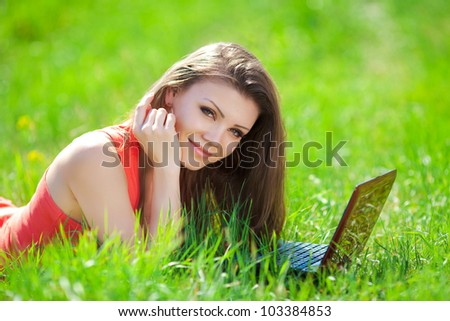 Portrait of a smart young woman lying on grass and using laptop