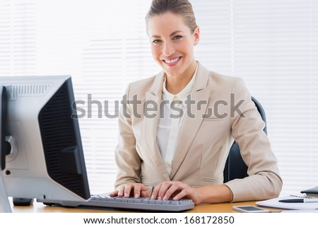 Portrait of a smartly dressed young businesswoman using computer at office desk