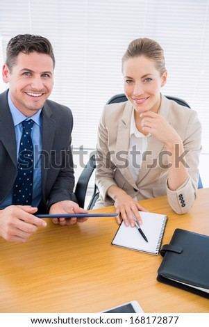 Portrait of a smartly dressed young man and woman in a business meeting at office desk