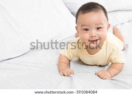 Portrait of a smile baby on the bed in his room - stock photo