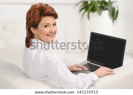 Portrait of a smiling adult female using a laptop while sitting on sofa at home