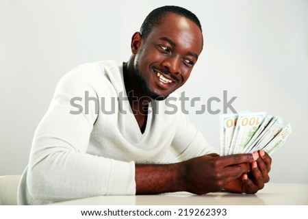 Portrait of a smiling african man holding US dollars