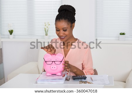 Portrait Of A Smiling African Woman Inserting Coin In Piggybank - stock photo