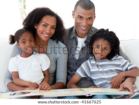 Portrait of a smiling Afro-American family reading a book in the living-room - stock photo