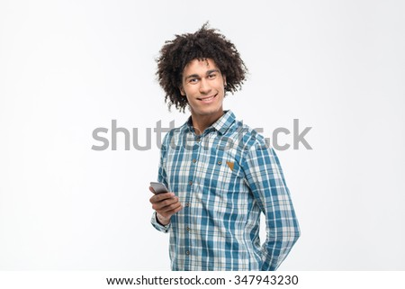 Portrait of a smiling afro american man holding smartphone and looking at camera isolated on a white background - stock photo