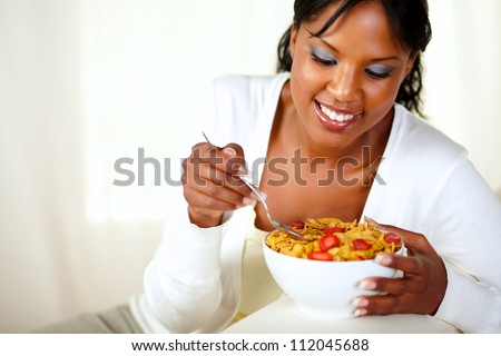Portrait of a smiling afro-american woman having healthy breakfast at home indoor. with copyspace - stock photo