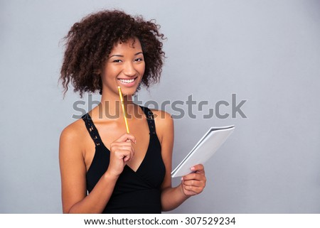 Portrait of a smiling afro american woman holding notebook with pencil over gray background - stock photo