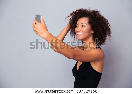 Portrait of a smiling afro american woman making selfie photo on smartphone over gray background - stock photo