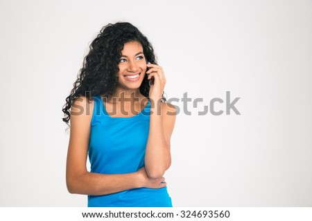 Portrait of a smiling afro american woman talking on the phone and looking away isolated on a white background - stock photo