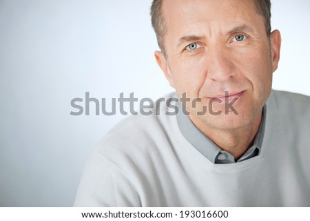 Portrait of a smiling and confident mature businessman, wearing a shirt and sweater in front of a gray wall with copy-space - stock photo