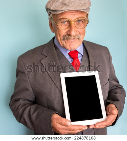 Portrait of a smiling and confident senior good looking business man holding tablet with empty display - stock photo